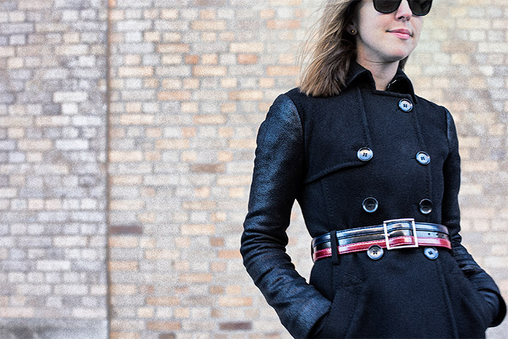3 Ways To Update Your Winter Coat- Put a Belt On it . Women's Fashion, black peacoat with leather sleeves, vintage leather belt, ray ban wayfarers, brick wall